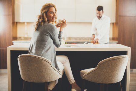 앉아있는 젊은 여자와 현대 부엌에서 정제의 사용하는 동안 식사를 준비하는 젊은 남자 스톡 콘텐츠