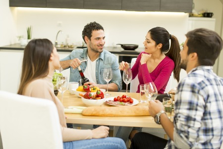 View at young people have a meal in the dining room in modern home Banco de Imagens