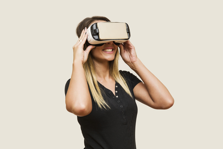 Young woman looking via virtual reality device in studio