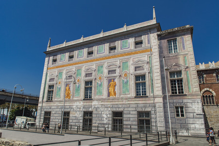 GENOA, ITALY - JUNE 2, 2015: Unidentified people by Palazzo San Giorgio in Genoa, Italy. Palace was built in 1260 and facade was refrescoed in the late 19th century Editorial