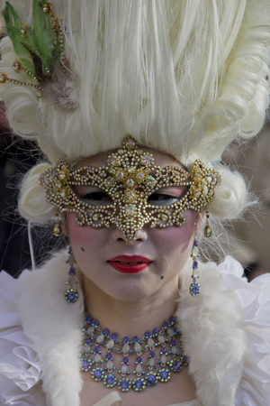 VENICE, ITALY - FEBRUARY 10, 2013: Unidentified woman with Venetian carnival mask in Venice, Italy. At 2013 it is held from January 26th to February 12th. Editorial