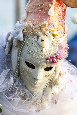 VENICE, ITALY - FEBRUARY  9, 2013: Unidentified person with Venetian carnival mask in Venice, Italy. At 2013 it is held from January 26th to February 12th. Publikacyjne