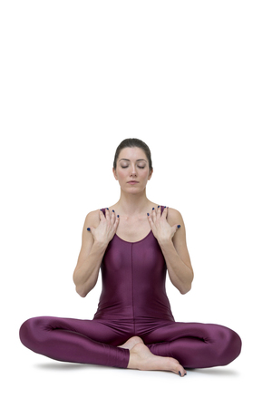 Young woman doing yoga in Vajrasana pose in studio
