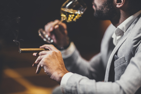Young man tasting white wine and smoking cigar Stock fotó - 80681409