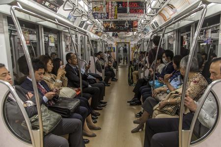 TOKYO, JAPAN - OKTOBER 12, 2016: Niet-geïdentificeerde mensen in de metrotrein van Tokyo. De metro van Tokyo heeft dagelijks 13 lijnen en 8,7 miljoen passagiers.