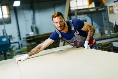 ハンサムな若い男の家具工場で働く