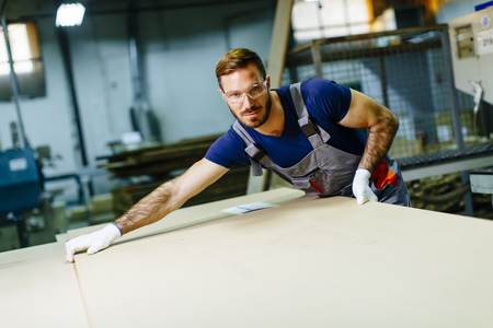 Handsome young man working in the furniture factory