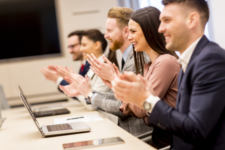 Happy smiling business team clapping hands during a meeting in office Stock Photo