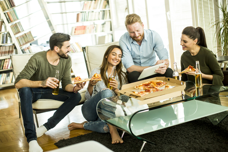 Group of young people eating pizza and drinking cider in the room Imagens