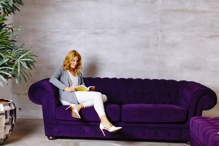自宅でカウチの絵本を読んで幸せな若い女性