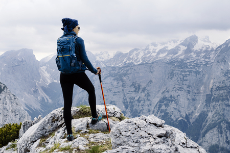 Female hiker standing on the top of the mountain with beatufil panorama below