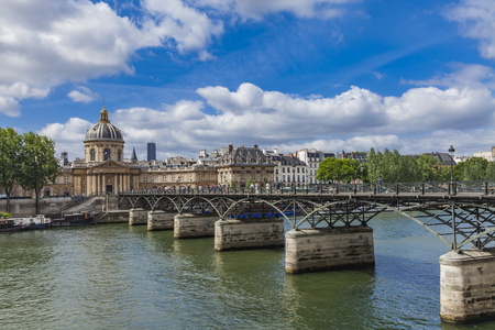 PARIS, FRANCE - JUNE 16, 2017: Unidentified people on the Pont des Arts in Paris, France. Bridge was opened in 1984 on the place of the first metal bridge in Paris.