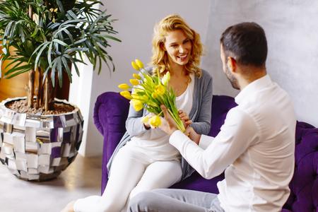 笑っている女性彼女の夫またはパートナーのソファーに座っていた彼に笑顔からチューリップを受信