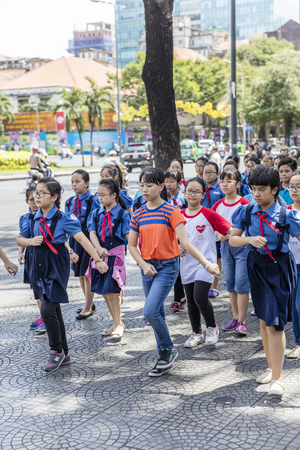 HO CHI MINH, VIETNAM - FEBRUARY 22, 2017: Unidentified school children marching on a street of ho Chi Minh, Vietnam. In Ho Chi Minh more than 97% of children attend primary school.