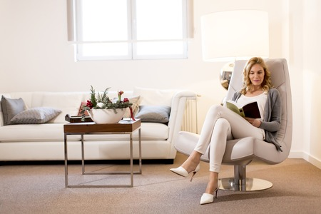 View at young woman reading a book and sitting on comfortable chair at home