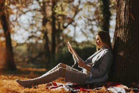 秋の公園で胎児の超音波画像を見て若い妊婦
