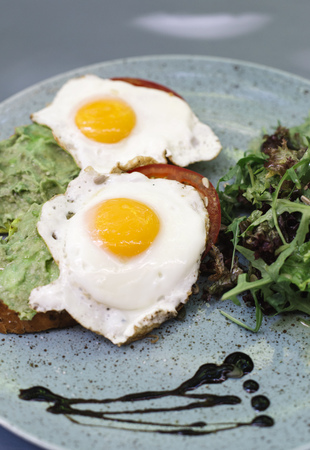 Close up view at fresh breakfest, fried eggs and salad on plate Stock Photo