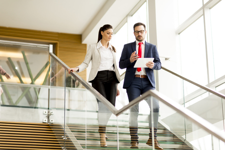 View at young businesswoman and businessman walk down stairs in office with a tablet in his hand