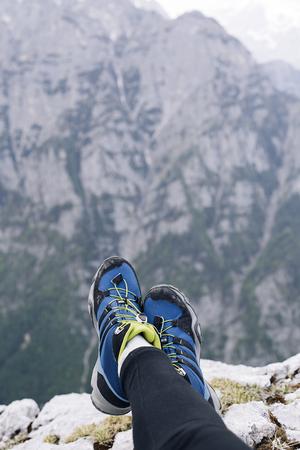 Female hikers shoes at the edge of a cliff. High above the mountains below Stock fotó