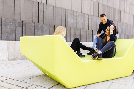 Young people sitting on the modern bench on street in Vienna, Austria