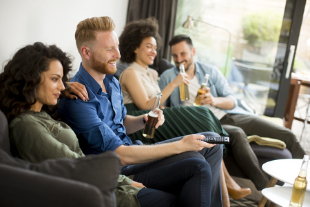 couch: Group of friends watching TV , drinking cider and having fun in the room