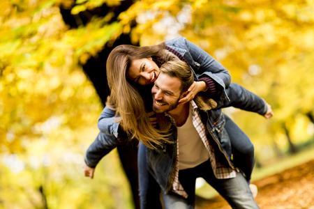 Jovem casal amoroso se divertindo no parque de outono em um dia ensolarado Foto de archivo - 82966384