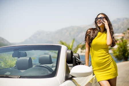 Pretty young woman in yellow dress with mobile phone by white cabriolet car