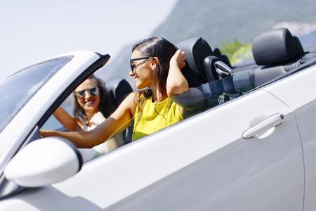 Twee gelukkige vrienden in een witte cabriolet auto rijden overal en op zoek naar vrijheid en plezier Stockfoto - 82418433