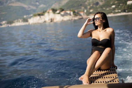 Pretty young woman relaxing on the yacht on sea at sunny day Stock Photo