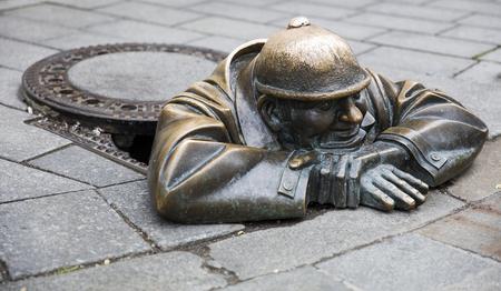 Bratislava, Slowakije - 16 juni 2017: Statue Man aan het werk in Bratislava, Slowakije. Dit bronzen beeld van rioolwerker is in 1997 door Viktor Hulik gemaakt.