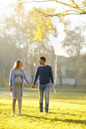 Young couple expecting baby and have fun with balloons in the autumn park
