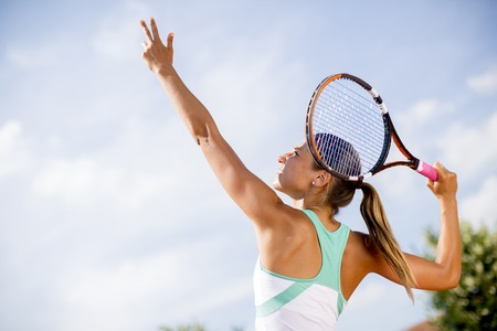 Young woman playing tennis on a sunny day