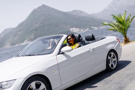 Twee gelukkige vrienden in een witte cabriolet auto rijden overal en op zoek naar vrijheid en plezier Stockfoto - 82966505