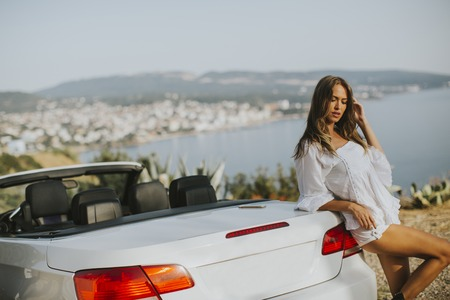View at young attractive woman poses next to a  cabriolet at seaside 版權商用圖片
