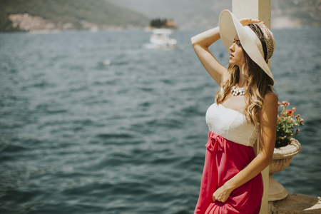 Young attractive woman in a dress relaxing by the sea at sunny day
