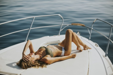 Young attractive woman lies and sunbathing on the bow of a luxury yacht Banco de Imagens - 83150837