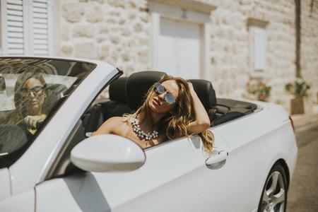 Twee gelukkige vrienden in een witte cabriolet auto rijden overal en op zoek naar vrijheid en plezier Stockfoto - 82967116