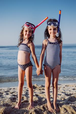 Niñas lindas con snorkel en la playa de arena en verano Foto de archivo - 83150844