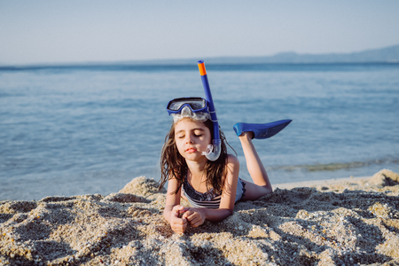 Cute little girl with snorkel set on the sandy beach at summer