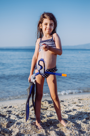 Linda niña con snorkel conjunto en la playa de arena en verano Foto de archivo - 82967106