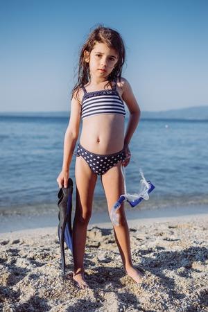 Petite petite amie avec tuba sur la plage de sable à l'été