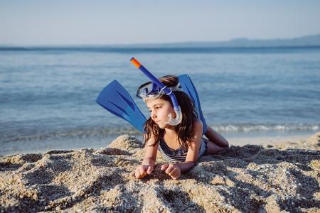 Linda niña con snorkel conjunto en la playa de arena en verano Foto de archivo - 83150829