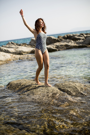 Pretty young woman at sea on the stony shore on a sunny day