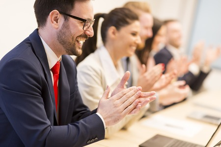 View at group of business people clapping their hands at the meeting