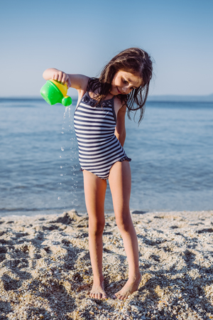 Cute little girl plaing with water on the sandy beach at summer Stock Photo