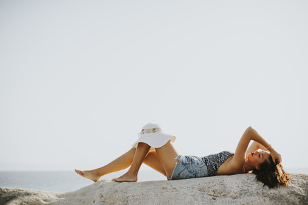 Pretty young woman on the stony beach at sunny day