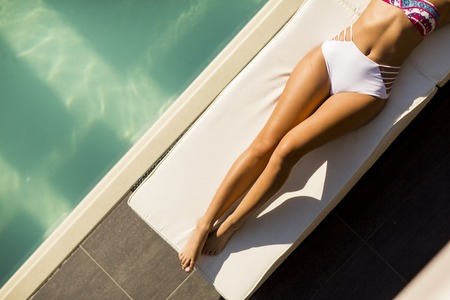 Pretty young woman relaxing on the bed by the swimming pool