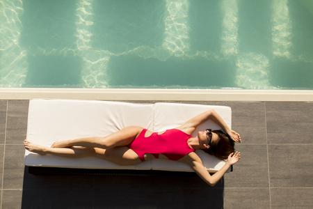 Jonge vrouw liggend bij het zwembad op bed