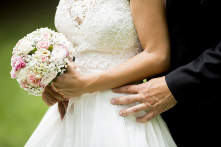 Wedding bouquet of roses in the hands of the bride Stock Photo
