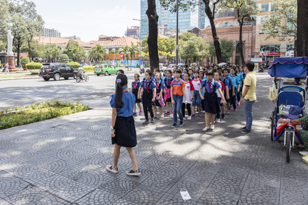 HO CHI MINH, VIETNAM - FEBRUARY 22, 2017: Unidentified school children marching on a street of ho Chi Minh, Vietnam. In Ho Chi Minh more than 97% of children attend primary school. Stock Photo - 83763974